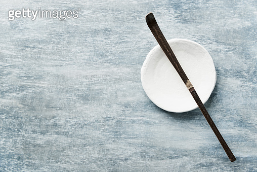 Chashaku Matcha spoon and empty ceramics plate on rustic wooden background. Symbolic image. Asian culture. Top view. Copy space.