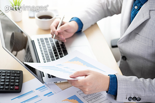 Businessman checking the business reports from the financial information from business document and laptop computer. Online business and economy concept.