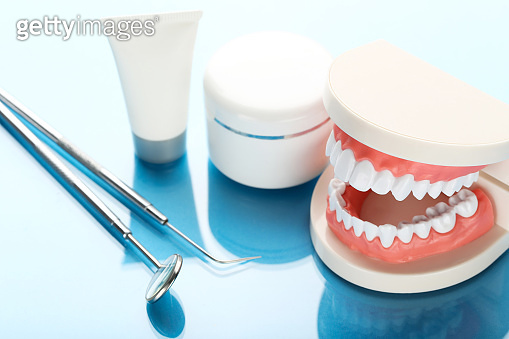 Teeth model with dental instruments and bottles on blue background