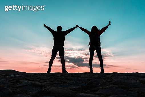 Couple silhouette with raised arms holding hands and looking at sunset