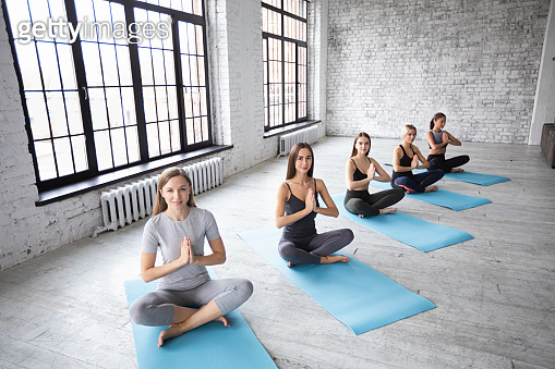 Yoga woman. Group of young beautiful girls doing meditation exercises in lotus position.