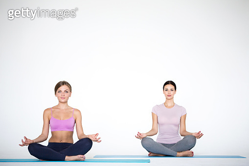 Young women sitting in lotus position indoors on white.