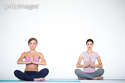 Young people do yoga sitting in lotus position indoors. Women hands in meditating gesture.