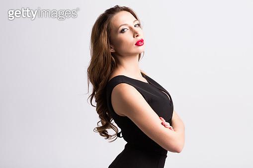 Young beautiful woman wearing black dress posing over grey