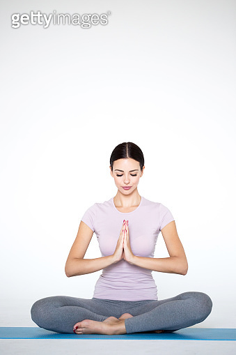 Beautiful young woman in sportswear practicing yoga while sitting in lotus position on white background.
