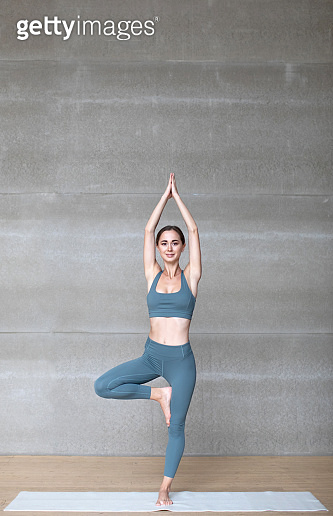 Beautiful young woman working out indoors, doing yoga exercise standing in Tree Pose full length.
