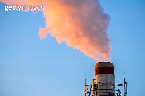 Bright orange smoke and steam from a high chimney of a power plant against a bright blue sky