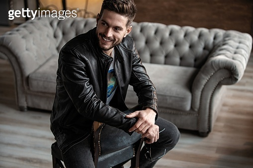 Handsome young man in leather jacket looking away while sitting on the stool