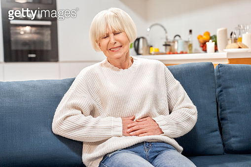Retirement. Senior woman sitting at home holding belyl wincing food poisoning