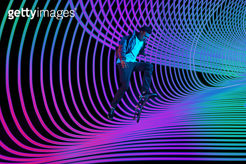 Caucasian young skateboarder riding on dark neon lighted line background