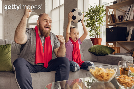 Excited, happy daughter and father watch football, soccer match together on the couch at home