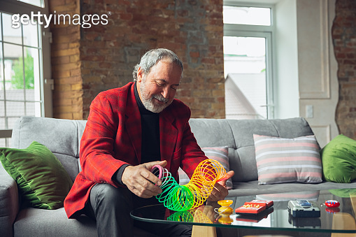 Portrait of senior man with retro toys, meeting things from the past and having fun, exploring the lifestyle of the nineties, playing with rainbow spring toy