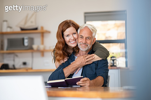 Senior happy couple embracing at home