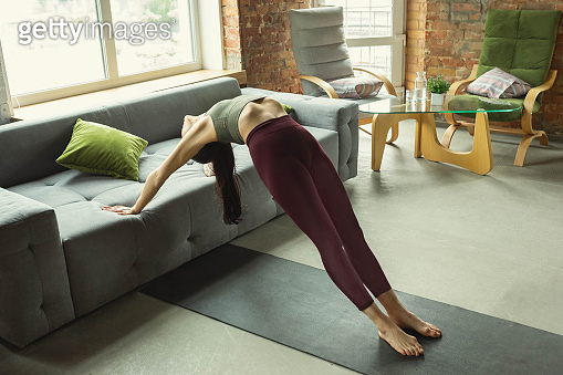 Sporty young woman practicing yoga at home
