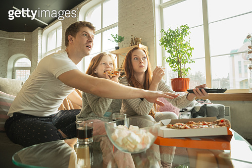 Family spending nice time together at home, looks happy and excited, eating pizza, watching sport match