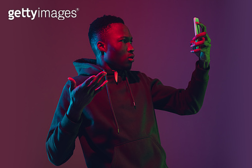 African-american man's portrait isolated on gradient studio background in neon light