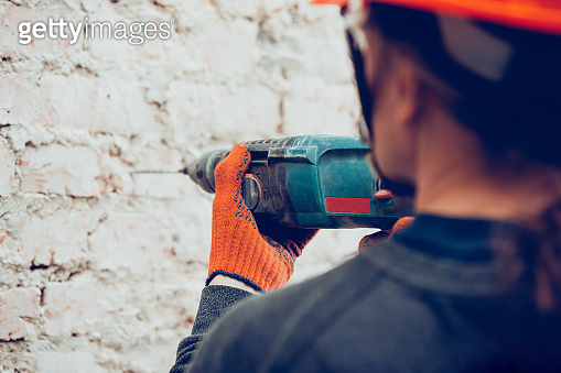 Close up of hands of repairman, professional builder working indoors, drills a wall