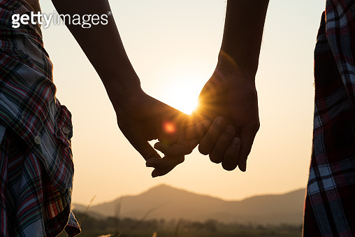 Close up of loving couple holding hands while walking at sunrise sunset in the meadow mountain in background. Valentine's Day and love concept.