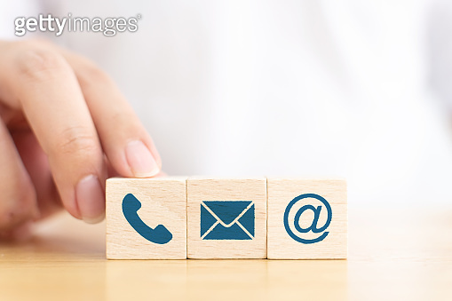 Businessman hand choose wooden block cube symbol icon telephone, envelope email and address sign. Website page contact us or e-mail marketing concept