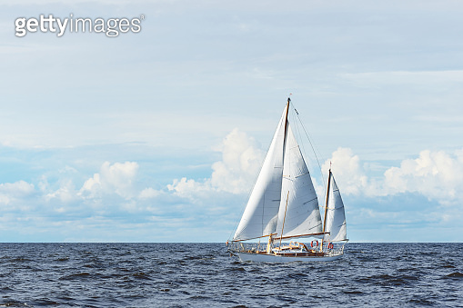 Old expensive vintage wooden sailboat (yawl) close-up, sailing in an open sea. Stunning cloudscape. Coast of Maine, US
