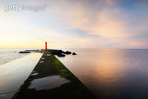An empty promenade to the orange lighthouse with solar battery against colorful sunset sky. Stunning cloudscape. Long exposure. Environmental conservation theme. Baltic sea, Riga bay, Latvia