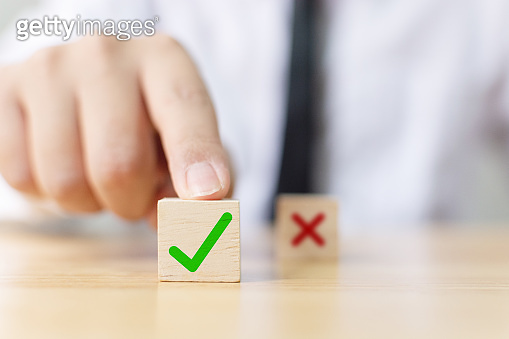 Hand of a businessman chooses checkmark and x sign symbol on wooden cube block