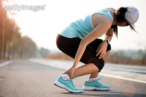 Ankle sprained. Young woman suffering from an ankle injury while exercising and running. Healthcare and sport concept.