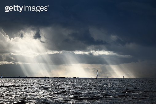 Sailing yacht regatta. Modern sailboat racing through the waves. Dramatic sky with flowing sun rays before the thunderstorm. Terrific cloudscape. North Germany, Kiel