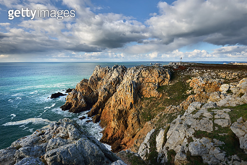 Aerial view of the rocky shore of Pointe de Pen-Hir, cliffs close-up. Cloudy blue sky, azure water, stormy waves. Dramatic cloudscape. Crozon peninsula, Brittany, France