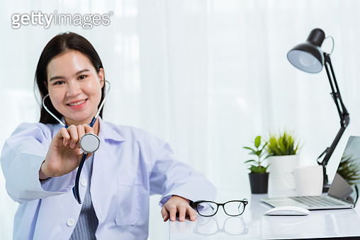 Portrait Asian confident female doctor working personal laptop computer at the hospital office. Thai woman medical expertise staff smiling hand to hold show stethoscope on desk space front computer