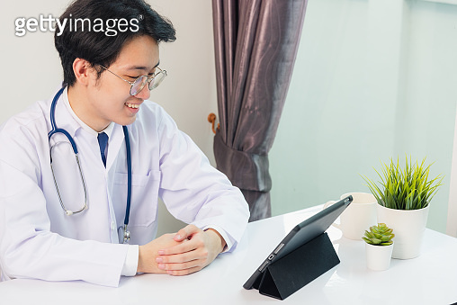 Happy Asian young doctor handsome man smile wear glasses use modern smart digital tablet computer sit and listen patient explain symptoms on desk at hospital office, Technology Healthcare And Medicine