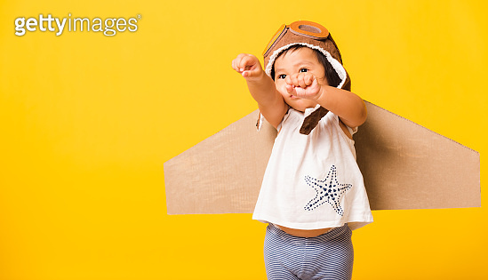 Kid little boy smile wear pilot hat play and goggles with toy cardboard airplane wings