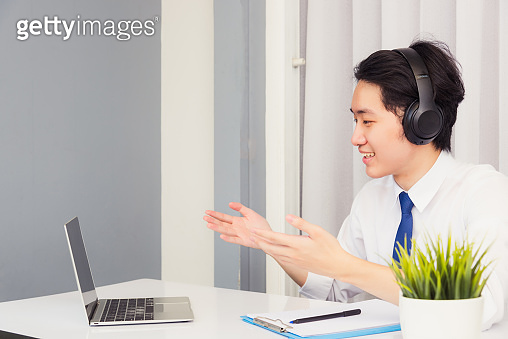 Asian young businessman smile wearing headphones and suit video conference call