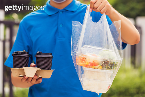 Delivery man wearing face mask making grocery giving rice food boxes plastic bags and coffee at front house