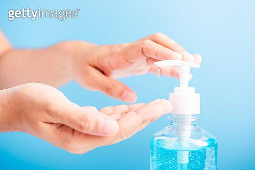 Close up woman applying press dispenser sanitizer alcohol gel pump to hand