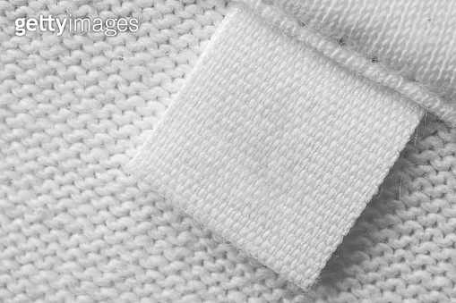 White blank laundry care clothes label on cotton shirt background