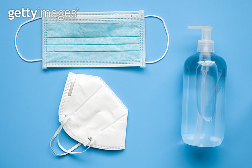 Alcohol hand sanitizer gel bottle with KN95 surgical face mask on blue background protection against COVID-19 coronavirus. Healthcare and medical concept