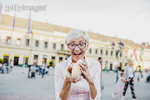 Happy elderly woman eating sausage roll