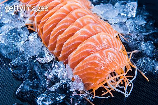 Fresh salmon sashimi on ice over black background. Japanese Food.