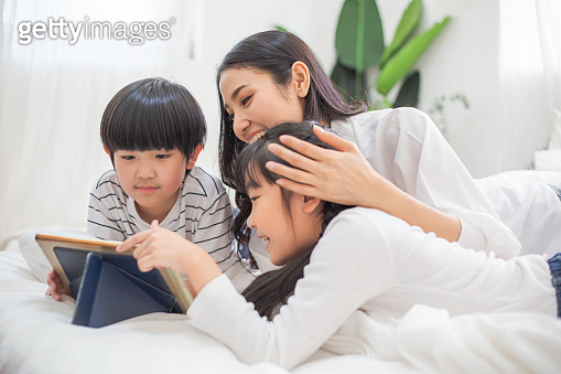 Happy family watching movie on screen. mother cuddle and take care son and daughter playing digital tablet. learning living with technology. stay home during Coronavirus or COVID19 lifestyle insurance