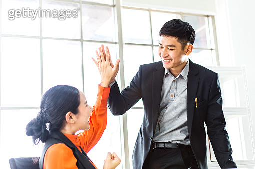 Happy successful Asian business man and woman giving high five for project success. corporate teamwork people connecting with partner in modern office. career opportunity. job promotion. copy space