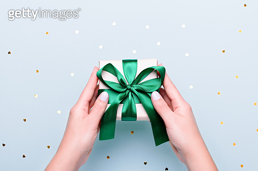 Woman holding gift box in green color on pastel blue background with heart shape confetti, copyspace. Valentine's Day or Women's Day greeting card in trendy colors, Happy Valentine Day background