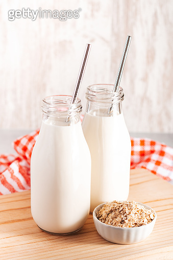 Non dairy oat milk in glass bottles with reusable metal straws. Healthy vegan milk alternative still life, copy space. Substitute for traditional cow milk with oat flakes, healthy lifestyle concept