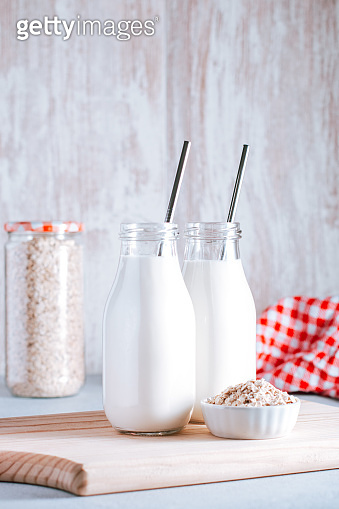 Non dairy oat milk in glass jars with reusable metal straws. Healthy vegan milk alternative still life, copy space. Substitute for traditional cow milk with oat flakes, healthy lifestyle concept