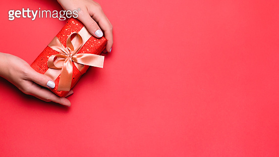 Woman holding gift box on red background, copyspace. Web banner, Valentine's Day greeting card, Mother's Day or Women's Day card in trendy colors, top view