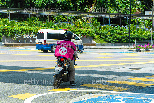 Courier of a popular food delivery service in Malaysia on a bike. Food ordering home