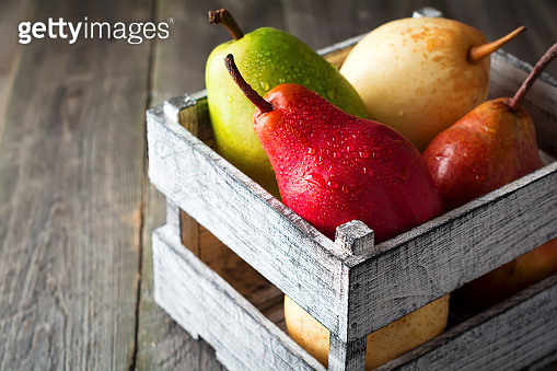 Red, green, yellow, sweet pear and one apple in the old wooden box on a dark background. Selective fokus.Rustik style