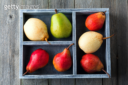 Red, green and yellow sweet pears in a wooden old box on a dark background. Selective focus.Top view.