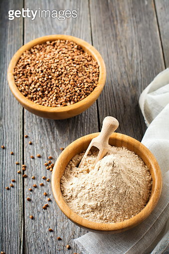 Buckwheat flour in a bamboo bowl on the old wooden background. Selective focus.