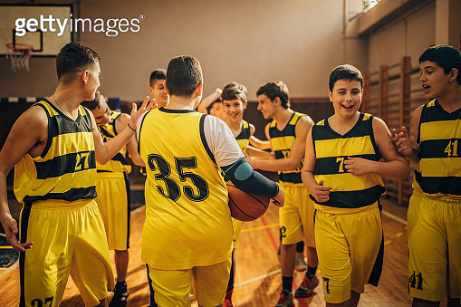 Young basketball team having fun together after training